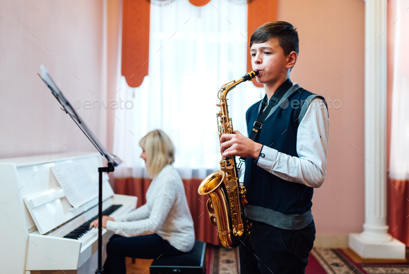 teenage boy learns to play the saxophone in a music lesson - Stock Photo - Images