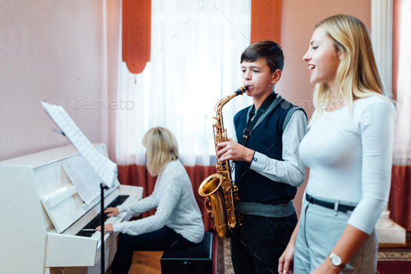 Boy student learns to play the saxophone in a music lesson to accompaniment of the piano. - Stock Photo - Images