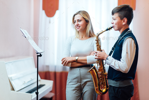 Cheerful teacher with student boy learning saxophone lessons at school - Stock Photo - Images