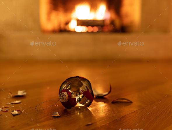 Christmas ball broken, blur burning fireplace background - Stock Photo - Images
