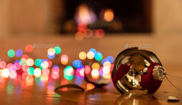 Christmas ball broken, colorful lights glowing, blur burning fireplace background - Stock Photo - Images