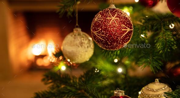 Christmas tree close up on burning fireplace background - Stock Photo - Images