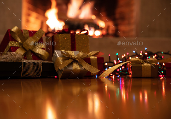 Christmas gifts and lights glowing, blur burning fireplace background - Stock Photo - Images