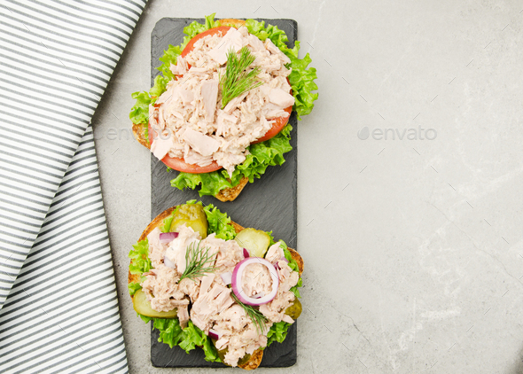 Flat lay view at Tuna sandwiches with lettuce tomatoes pickles and onions on slate tray - Stock Photo - Images