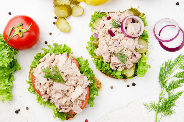 Flat lay view at Tuna sandwiches with lettuce tomatoes pickles and onions on parchment paper - Stock Photo - Images