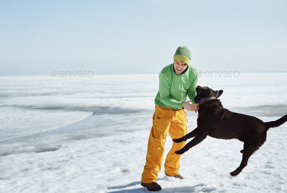Young adult man outdoors with his dog having fun in winter landscape - Stock Photo - Images