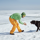 Young adult man outdoors with his dog having fun in winter landscape - PhotoDune Item for Sale