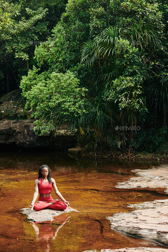 Young woman meditating in forest - Stock Photo - Images
