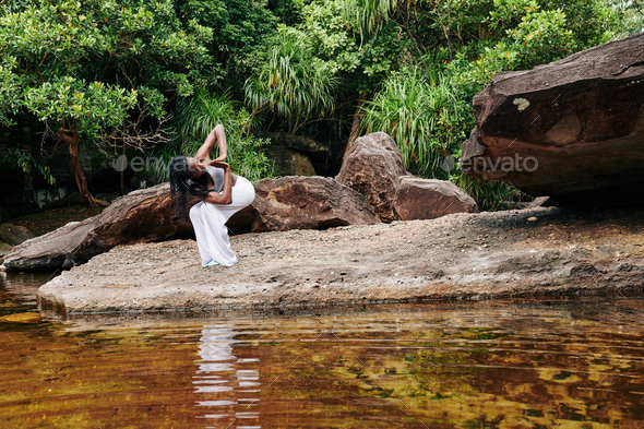 Woman exercising in forest by the creek - Stock Photo - Images