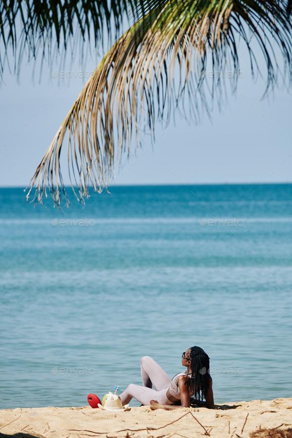 Sportswoman resting on beach - Stock Photo - Images