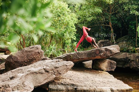 Woman doing one-legged upward facing dog pose - Stock Photo - Images