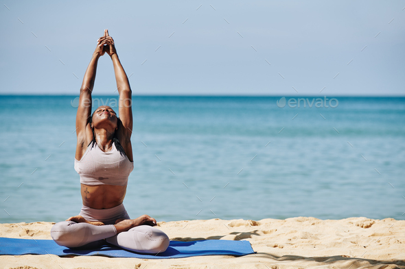 Woman stretching on the beach - Stock Photo - Images