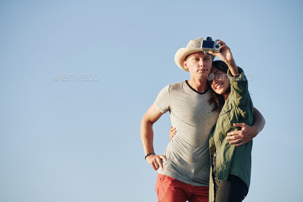 Hugging couple taking selfie - Stock Photo - Images