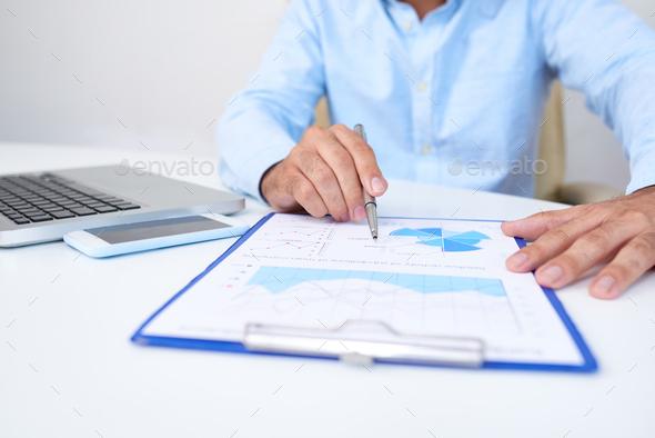 Business executive analyzing diagram - Stock Photo - Images