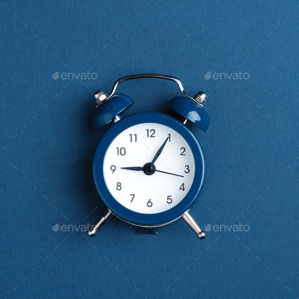 Classic Alarm Clock on Blue Background. - Stock Photo - Images