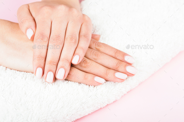 Female's Hands with Classic Pastel Manicure on White Towel. - Stock Photo - Images