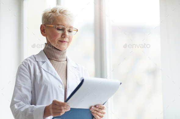 Portrait of Female Doctor Holding Clipboard by Window - Stock Photo - Images