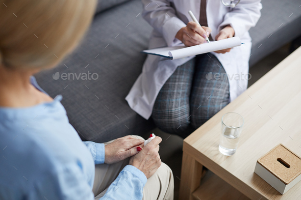 Unrecognizable Female Doctor Writing on Clipboard in Consultation - Stock Photo - Images