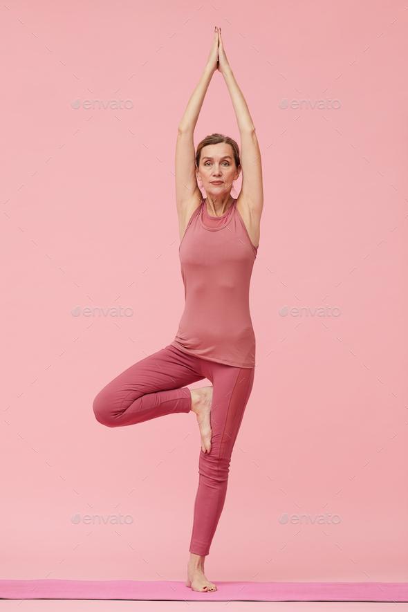 Mature Woman Enjoying Yoga on Pink - Stock Photo - Images
