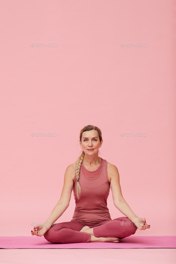 Mature Woman Sitting in Lotus Position on Pink - Stock Photo - Images