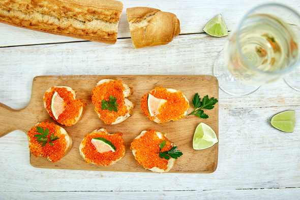 Salmon red caviar in bowl and Sandwiches with on wooden cutting board - Stock Photo - Images
