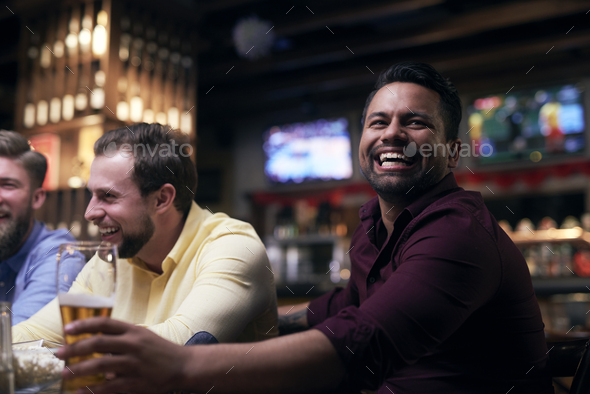 Men watching american football in the pub - Stock Photo - Images