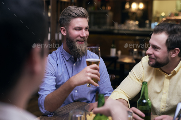 Male friends spending time together in the pub - Stock Photo - Images