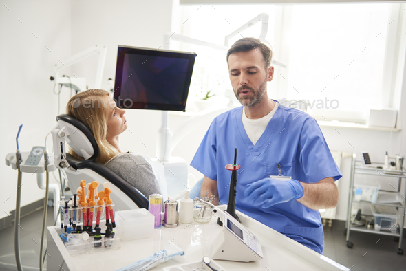 Male dentist doing him work in dentist's clinic - Stock Photo - Images