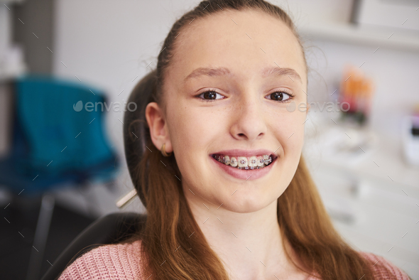 Portrait of smiling child with braces in dentist's office - Stock Photo - Images