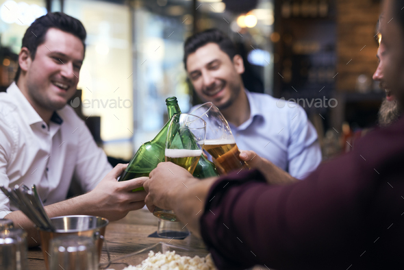 Men making a cheers in the pub - Stock Photo - Images