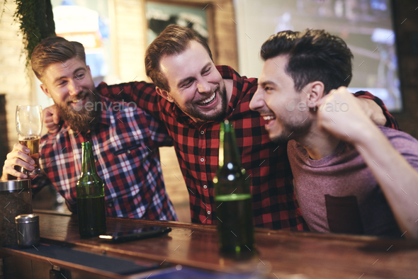Three men enjoying time together in the pub - Stock Photo - Images