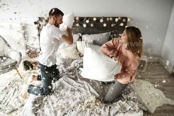 Happy couple during pillow fight among plumage falling - Stock Photo - Images
