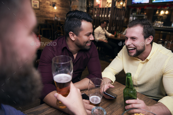 Male friends chilling with drinks at the bar - Stock Photo - Images