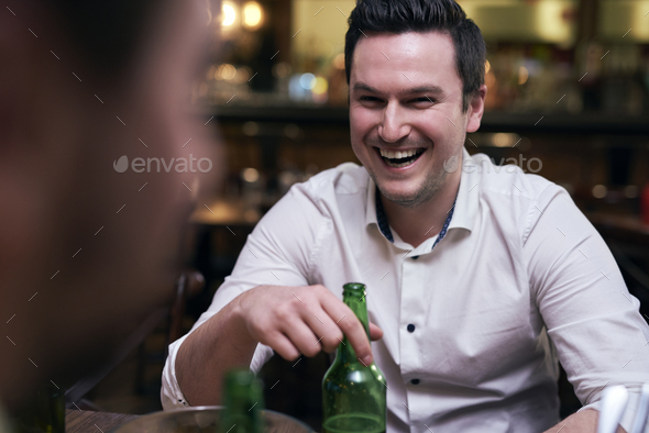 Joyful man drinking beer in the pub - Stock Photo - Images