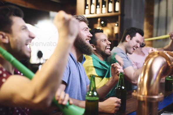 Happy men while watching american football - Stock Photo - Images