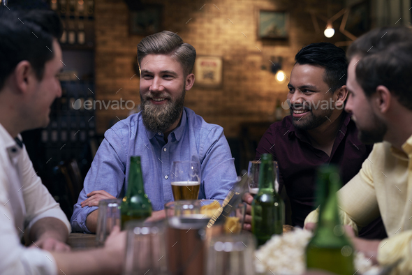 Mature man catches attention of his friends - Stock Photo - Images