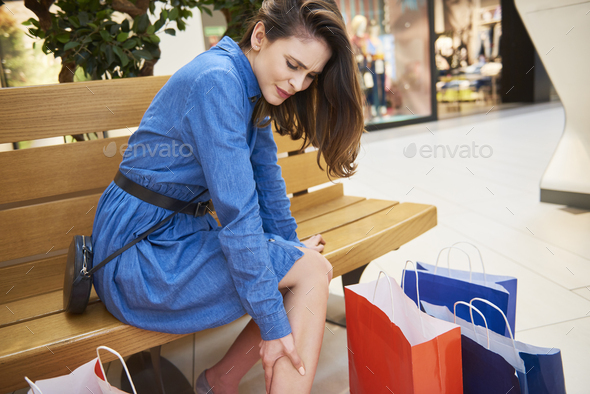 Woman suffering from leg pain during shopping - Stock Photo - Images