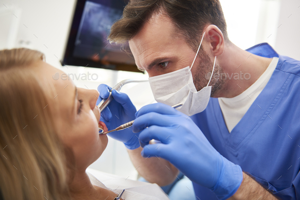 Focused stomatologist treating woman for dental cavity - Stock Photo - Images