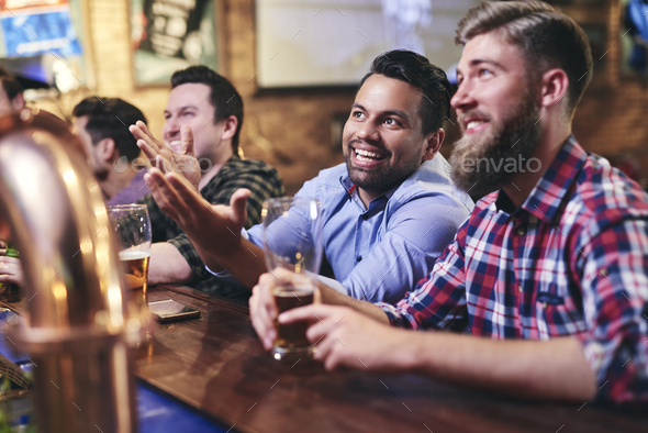 Mature men watching the football game at the bar - Stock Photo - Images