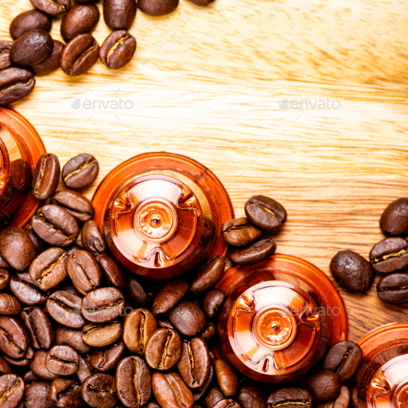 Espresso coffee capsules or pods and coffee beans on wooden rustic background - Stock Photo - Images