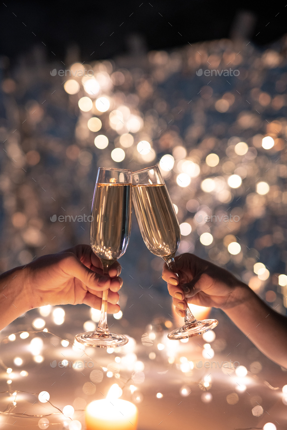 Hands of young couple clinking with flutes of champagne on xmas background - Stock Photo - Images