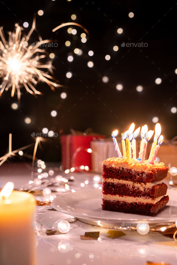 Piece of cake with many burning candles on plate surrounded by sparkling lights - Stock Photo - Images