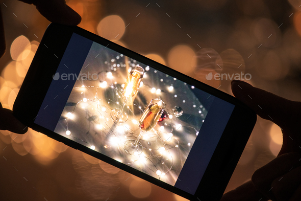 Human hands holding smartphone with image of two flutes of champagne on table - Stock Photo - Images
