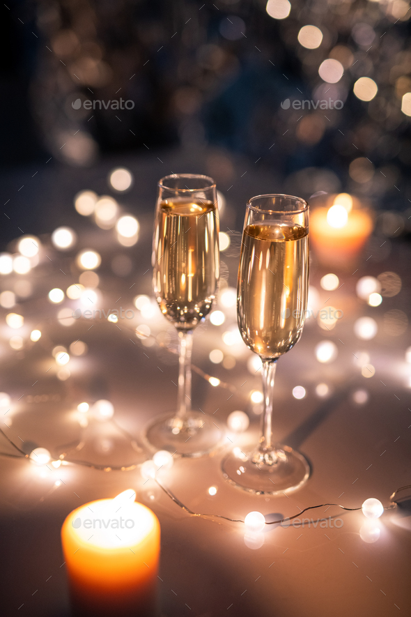 Two crystal flutes of champagne surrounded by lit garlands and burning candles - Stock Photo - Images