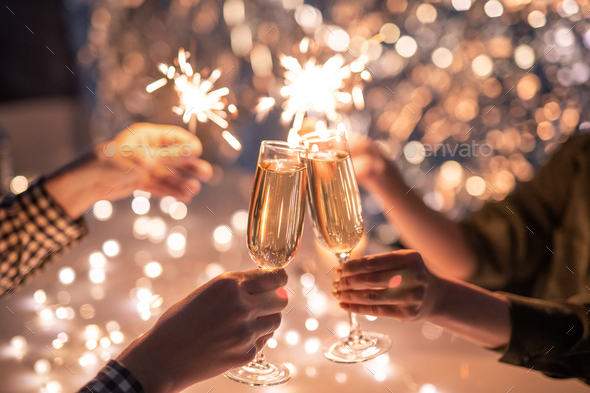 Hands of couple with flutes of champagne and their friends with bengal lights - Stock Photo - Images