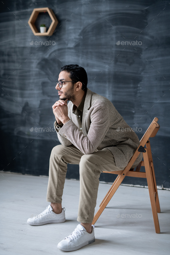 Young pensive businessman in smart casual sitting on chair in front of camera - Stock Photo - Images