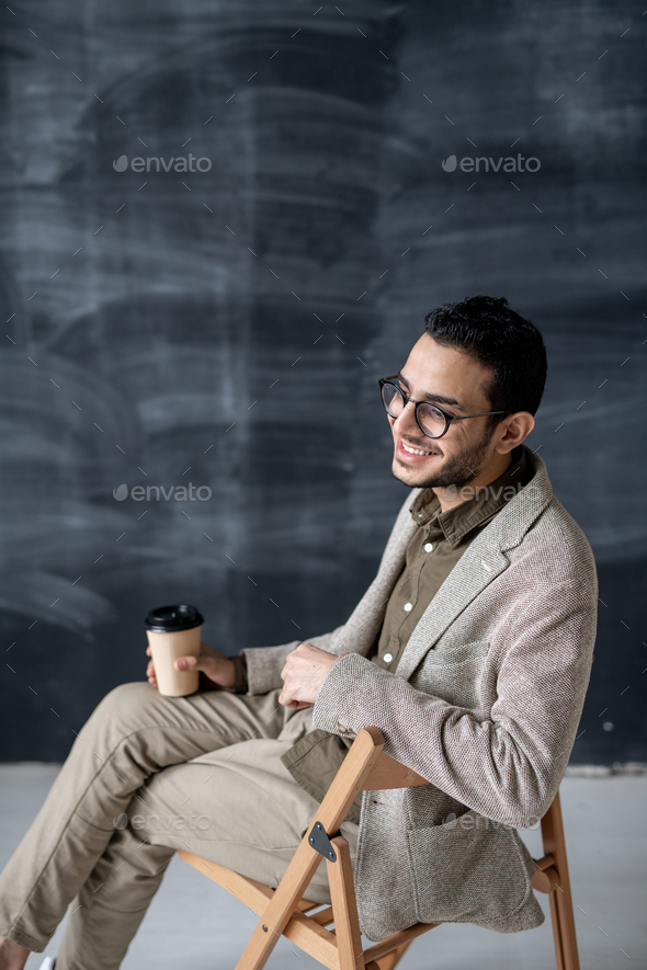 Cheerful man in eyeglasses and smart casual having drink while sitting on chair - Stock Photo - Images