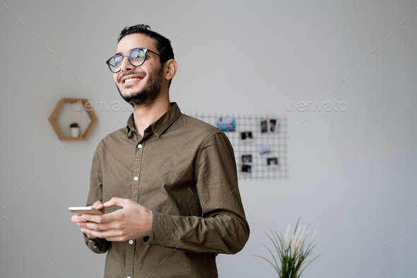 Young cheerful businessman in eyeglasses and casual shirt scrolling in the phone - Stock Photo - Images