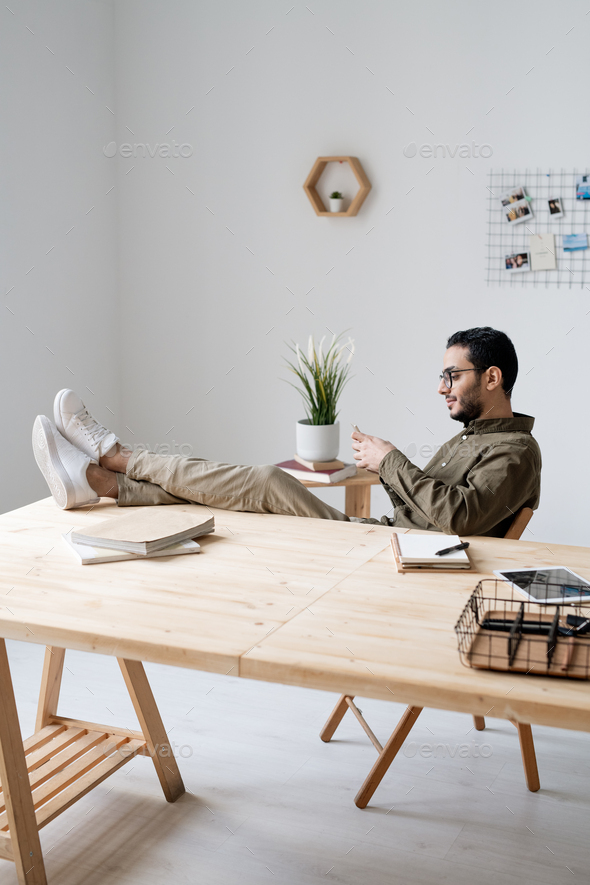 Young employee with smartphone sitting by workplace with his legs on table - Stock Photo - Images