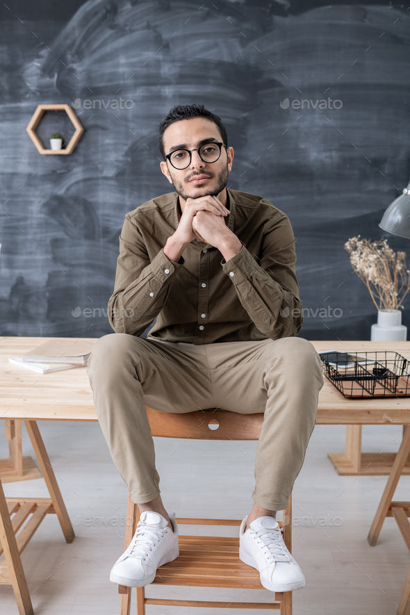 Young restful businessman in casualwear looking at you while sitting on table - Stock Photo - Images